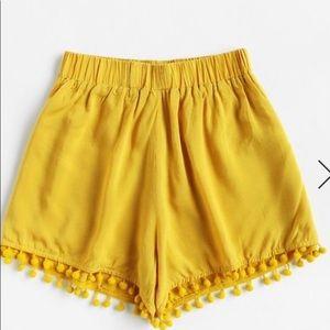 Yellow high waisted shorts with fringe hanging